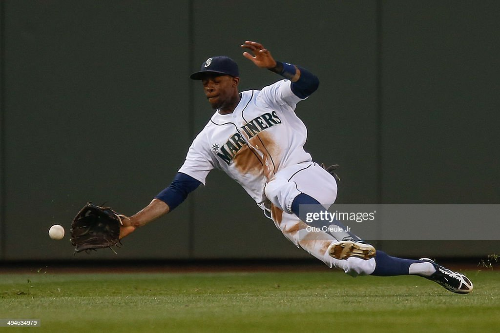 Center fielder James Jones of the Seattle Mariners attempts to field a triple off the bat of Raul Ibanez of the Los Angeles Angels of Anaheim in the...