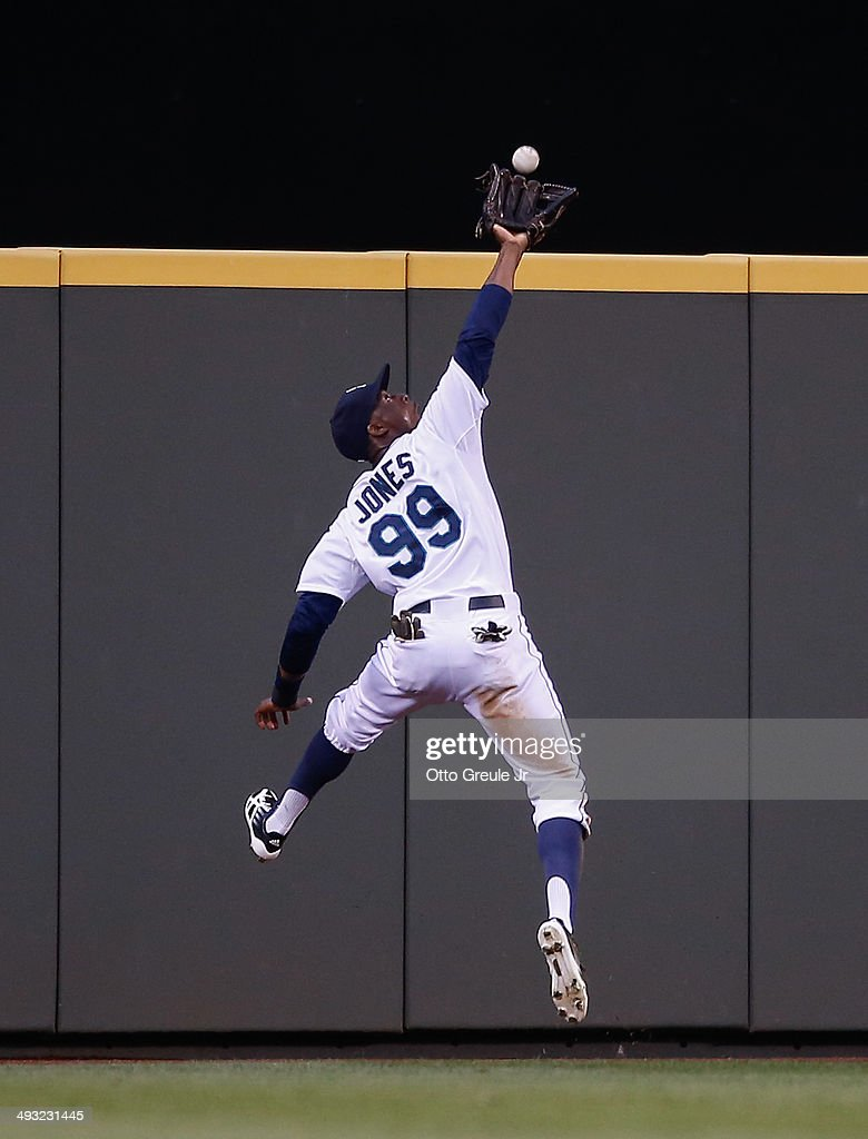 Center fielder James Jones of the Seattle Mariners makes a leaping catch on a ball off the bat of Alex Presley of the Houston Astros in the fourth...