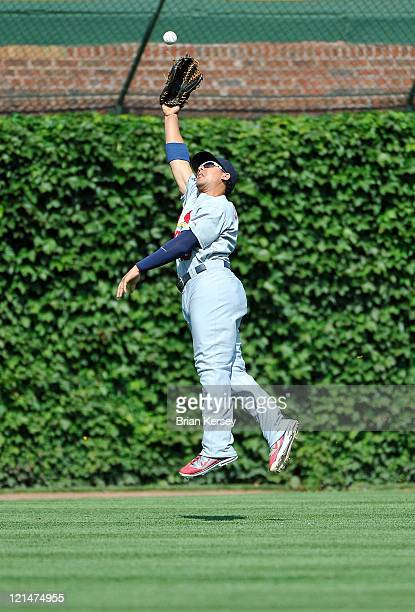 Center fielder Jon Jay of the St Louis Cardinals leaps for but cannot catch an RBI triple hit by Blake DeWitt of the Chicago Cubs scoring teammate...