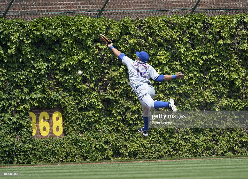 Center fielder Juan Lagares #12 of the New York Mets reaches for, but cannot get to a leadoff double hit by David DeJesus #9 of the Chicago Cubs during the first inning on May 19, 2013 at Wrigley Field in Chicago, Illinois.