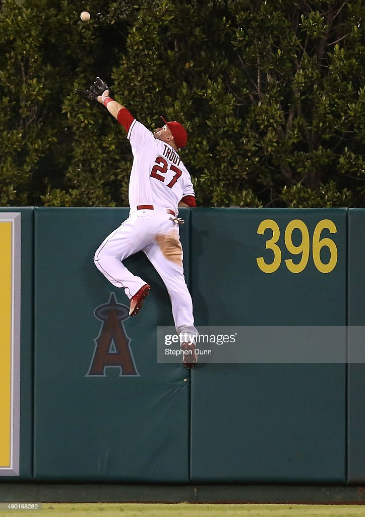 Center fielder <a gi-track='captionPersonalityLinkClicked' href=/galleries/search?phrase=Mike+Trout&family=editorial&specificpeople=7091306 ng-click='$event.stopPropagation()'>Mike Trout</a> #27 of the Los Angeles Angels of Anaheim jumps at the wall and makes the catch to take a home away from Jesus Montero of the Seattle Mariners in the fourth inning at Angel Stadium of Anaheim on September 26, 2015 in Anaheim, California.