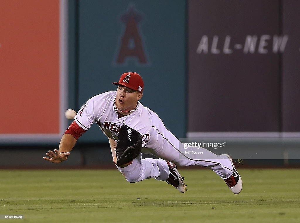 Center fielder <a gi-track='captionPersonalityLinkClicked' href=/galleries/search?phrase=Mike+Trout&family=editorial&specificpeople=7091306 ng-click='$event.stopPropagation()'>Mike Trout</a> #27 of the Los Angeles Angels of Anaheim makes a diving catch on a ball hit by Yoenis Cespedes of the Oakland Athletics in the fifth inning at Angel Stadium of Anaheim on September 11, 2012 in Anaheim, California.