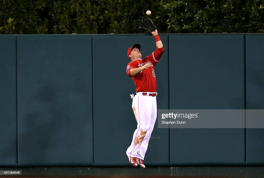 Center fielder <a gi-track='captionPersonalityLinkClicked' href=/galleries/search?phrase=Mike+Trout&family=editorial&specificpeople=7091306 ng-click='$event.stopPropagation()'>Mike Trout</a> #27 of the Los Angeles Angels of Anaheim makes a leaping catch on a deep fly ball hit by Eduardo Escobar of the Minnesota Twins to end the Twins' eighth inning at Angel Stadium of Anaheim on June 24, 2014 in Anaheim, California.