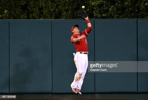 Center fielder Mike Trout of the Los Angeles Angels of Anaheim makes a leaping catch on a deep fly ball hit by Eduardo Escobar of the Minnesota Twins...