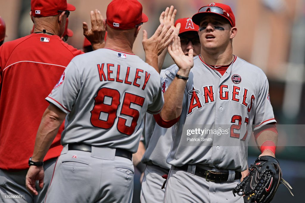 Center fielder <a gi-track='captionPersonalityLinkClicked' href=/galleries/search?phrase=Mike+Trout&family=editorial&specificpeople=7091306 ng-click='$event.stopPropagation()'>Mike Trout</a> #27 of the Los Angeles Angels of Anaheim celebrates with coaches and teammates after defeating the Baltimore Orioles at Oriole Park at Camden Yards on June 12, 2013 in Baltimore, Maryland. The Los Angeles Angels of Anaheim won, 9-5.