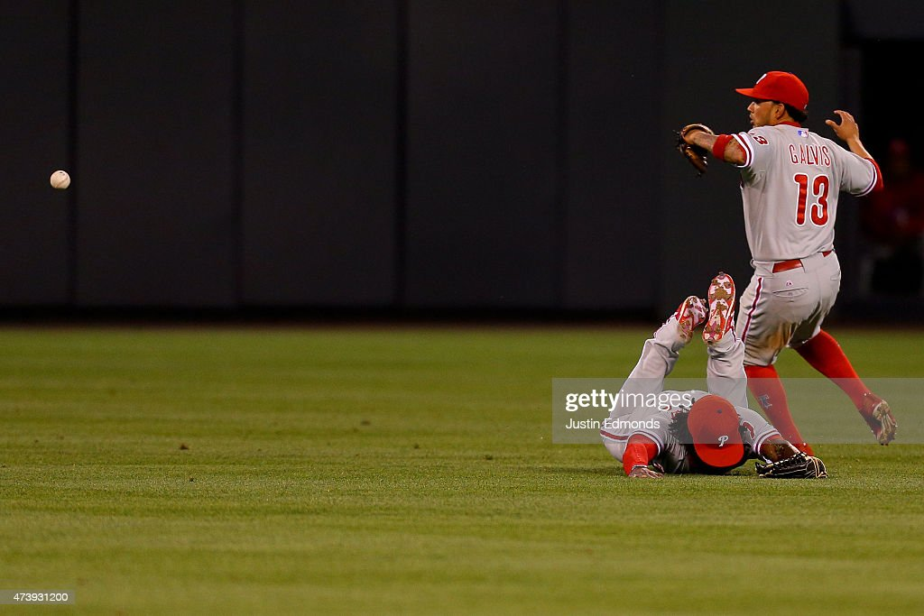 Center fielder Odubel Herrera #37 of the Philadelphia Phillies face plants into the ground after coming up short on a double off the bat of Drew Stubbs (not pictured) of the Colorado Rockies as shortstop Freddy Galvis #13 tracks down the baseball during the fourth inning at Coors Field on May 18, 2015 in Denver, Colorado.