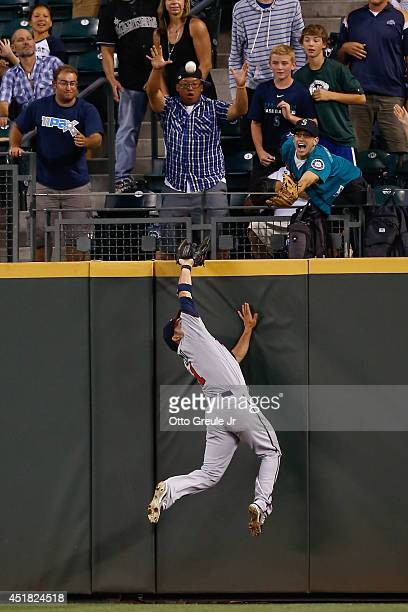 Center fielder Sam Fuld of the Minnesota Twins slams into the wall attempting to catch a home run off the bat of Michael Saunders of the Seattle...