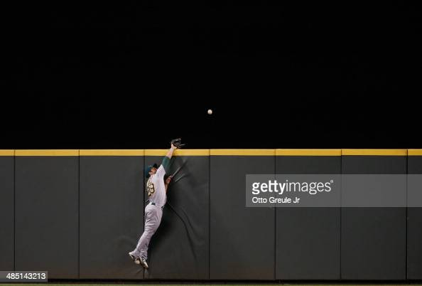 Center fielder Sam Fuld of the Oakland Athletics reaches for a home run ball off the bat of Brad Miller of the Seattle Mariners at Safeco Field on...