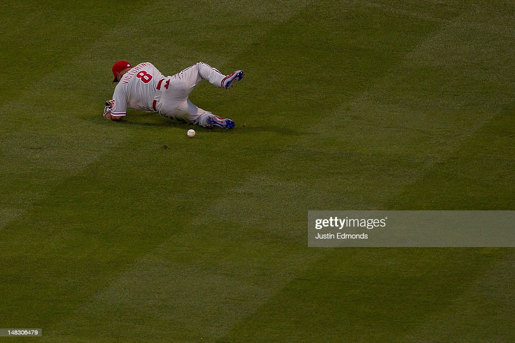 Center fielder <a gi-track='captionPersonalityLinkClicked' href=/galleries/search?phrase=Shane+Victorino&family=editorial&specificpeople=576251 ng-click='$event.stopPropagation()'>Shane Victorino</a> #8 of the Philadelphia Phillies misplays a ball hit by Tyler Colvin of the Colorado Rockies that went for a double in the sixth inning at Coors Field on July 13, 2012 in Denver, Colorado. Colvin went on to score the go-ahead run later in the inning.