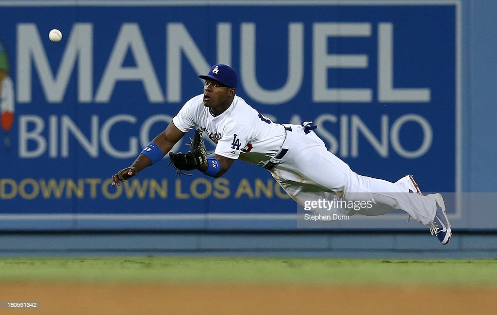 Center fielder Yasiel Puig of the Los Angeles Dodgers makes a diving catch on a line drive with the bases loaded by Buster Posey of the San Francisco...