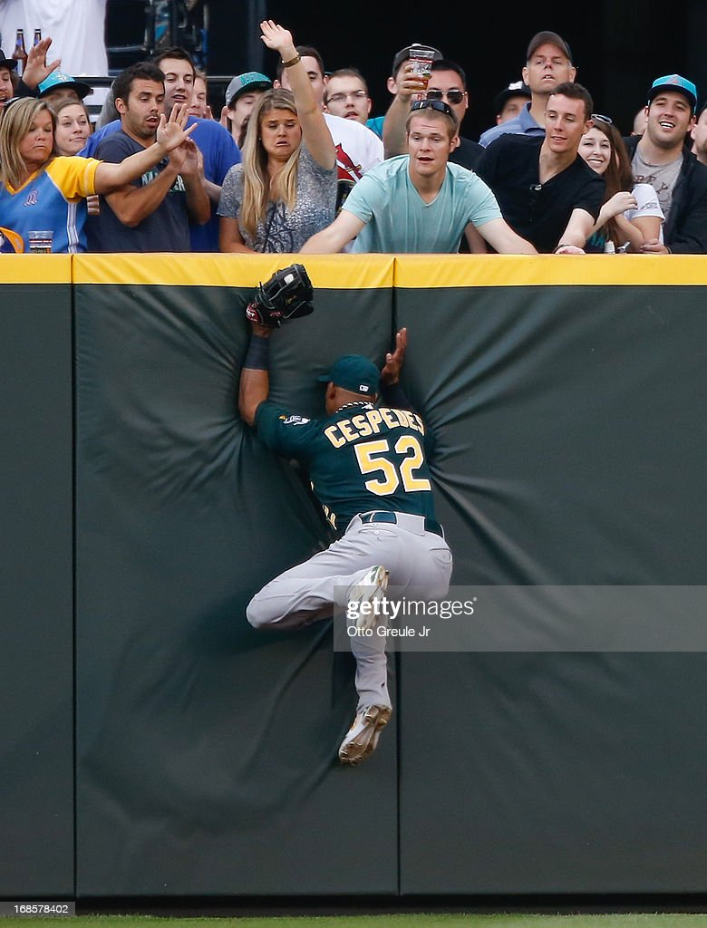 Center fielder <a gi-track='captionPersonalityLinkClicked' href=/galleries/search?phrase=Yoenis+Cespedes&family=editorial&specificpeople=8892047 ng-click='$event.stopPropagation()'>Yoenis Cespedes</a> #52 of the Oakland Athletics crashes into the wall as he catches a deep fly ball by Kyle Seager of the Seattle Mariners in the sixth inning at Safeco Field on May 11, 2013 in Seattle, Washington.