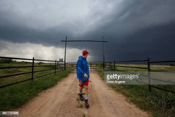 Center for Severe Weather Research intern Hunter Anderson heads back to the tornado scout vehicle after taking photographs of a supercell...