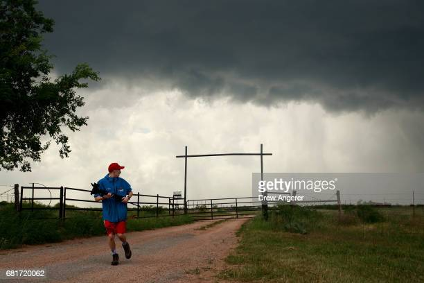 Center for Severe Weather Research intern Hunter Anderson hustles back to the tornado scout vehicle as a supercell thunderstorm develops May 10 2017...
