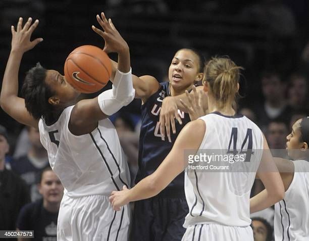 Center Kiah Stokes of Connecticut battles forward Talia East and Tori Waldner of Penn State in the first half at the Bryce Jordan Center in State...