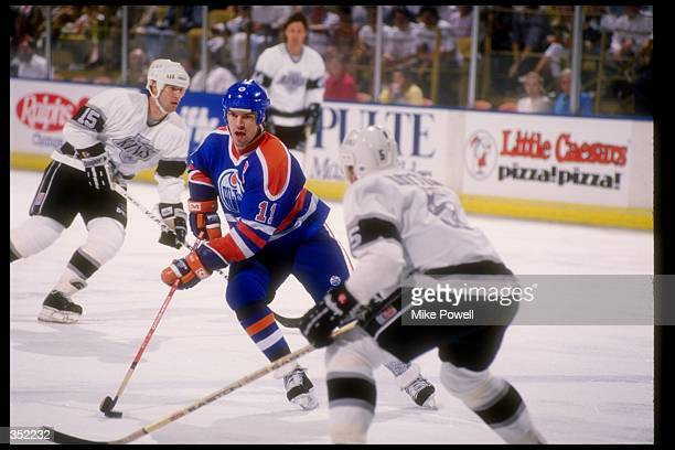 Center Mark Messier of the Edmonton Oilers moves the puck during a game against the Los Angeles Kings at the Great Western Forum in Inglewood...