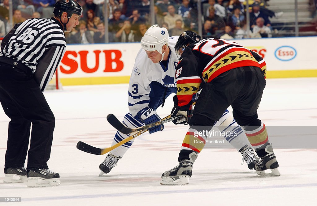 Center Mats Sundin #13 of the Toronto Maple Leafs and center Todd White #28 of the Ottawa Senators wait for linesman Brad Lazarowich #86 to drop the puck for a face off during the game on October 12, 2002 at Air Canada Centre in Toronto, Ontario, Canada.