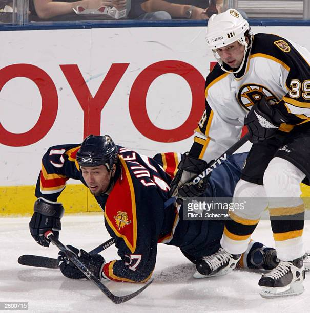 Center Matt Cullen of the Florida Panthers is tripped by Center Travis Green of the Boston Bruins in NHL action on December 10 2003 at the Office...