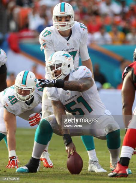 Center Mike Pouncey of the Miami Dolphins prepares to snap the ball to quarterback Ryan Tannehill against the Atlanta Falcons at Sun Life Stadium on...