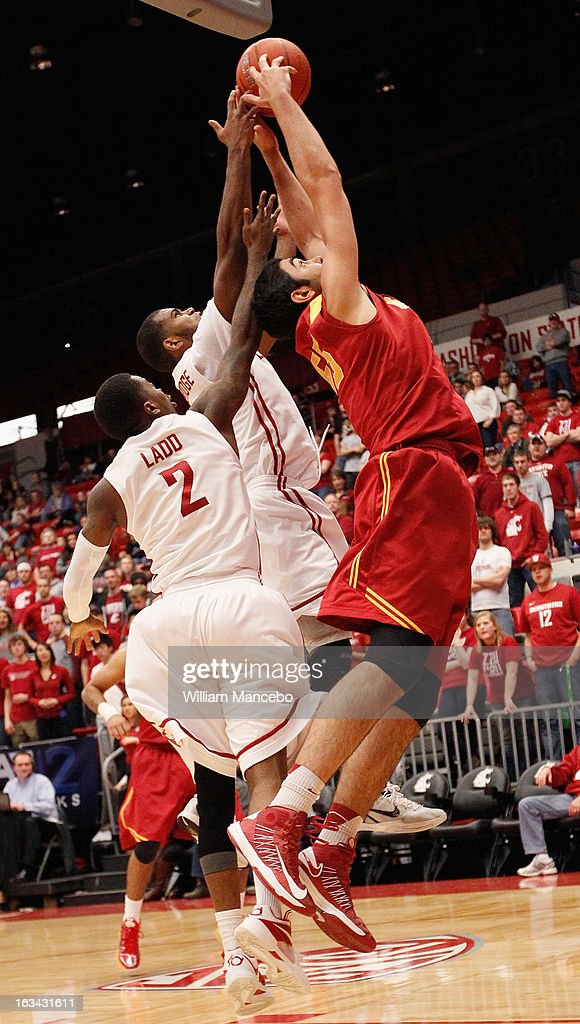 Center Omar Oraby #55 of the USC Trojans reaches for an offensive rebound against guards Mike Ladd #2 and Royce Woolridge #22 of the Washington State Cougars during the game at Beasley Coliseum on March 9, 2013 in Pullman, Washington.