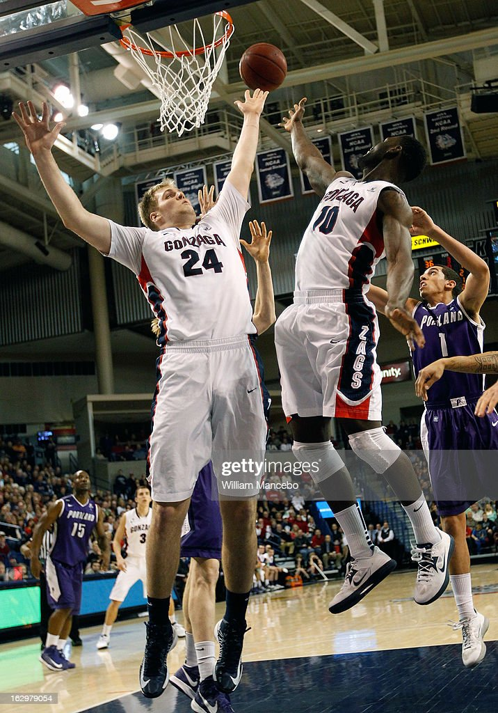 Center Przemek Karnowski #24 and forward Guy Landry Edi #10 of the Gonzaga Bulldogs attempt to grab an offensive rebound during the second half of the game against the Portland Pilots at McCarthey Athletic Center on March 2, 2013 in Spokane, Washington.