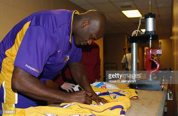 Center Shaquille O'Neal of the Los Angeles Lakers autographs a uniform in the hallway outside the locker room at First Union Center before the game...