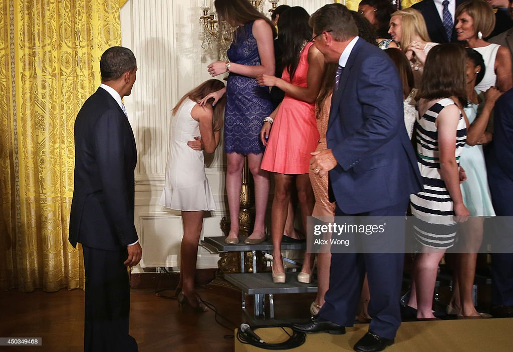 Center Stefanie Dolson (2nd L) of the University of Connecticut women's basketball team hides as U.S. President Barack Obama (L) looks on after she slipped off the riser during an East Room event at the White House June 9, 2014 in Washington, DC. President Obama hosted the NCAA Champion UConn Huskies Men's and Women's basketball teams to honor the teams and their 2014 NCAA Championships.