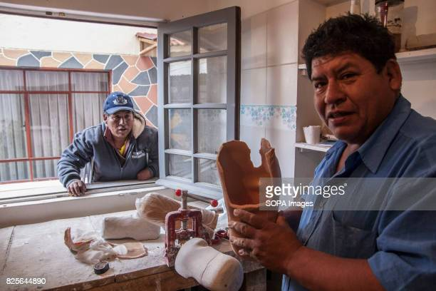 A center worker taps Pedro's leg mold which looks intently at the other side of the window Bolivian farmers walk again with the help of prostheses