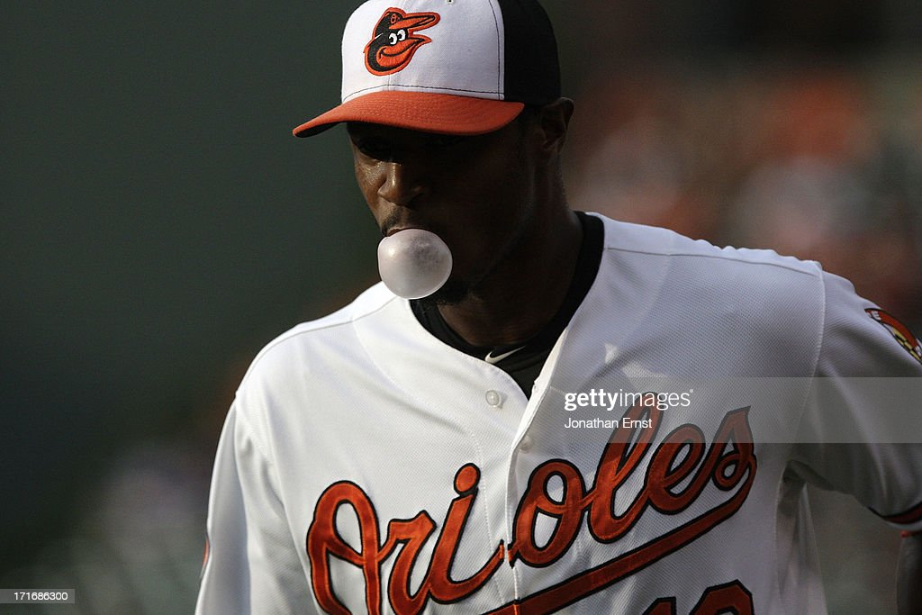 Centerfielder Adam Jones #10 of the Baltimore Orioles blows a bubble with his gum as he warms up before the start of a game against the Cleveland Indians at Oriole Park at Camden Yards on June 27, 2013 in Baltimore, Maryland.