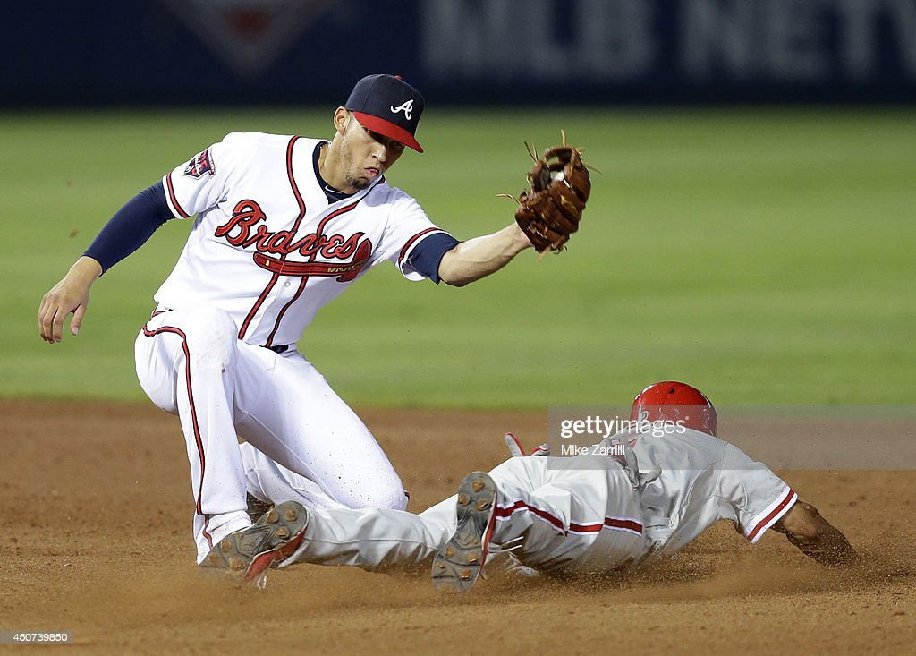 Centerfielder <a gi-track='captionPersonalityLinkClicked' href=/galleries/search?phrase=Ben+Revere&family=editorial&specificpeople=6826641 ng-click='$event.stopPropagation()'>Ben Revere</a> #2 of the Philadelphia Phillies slides into second base under the tag of shortstop <a gi-track='captionPersonalityLinkClicked' href=/galleries/search?phrase=Andrelton+Simmons&family=editorial&specificpeople=8978424 ng-click='$event.stopPropagation()'>Andrelton Simmons</a> #19 of the Atlanta Braves in the 13th inning during the game at Turner Field on June 16, 2014 in Atlanta, Georgia. Revere scored the go ahead run.