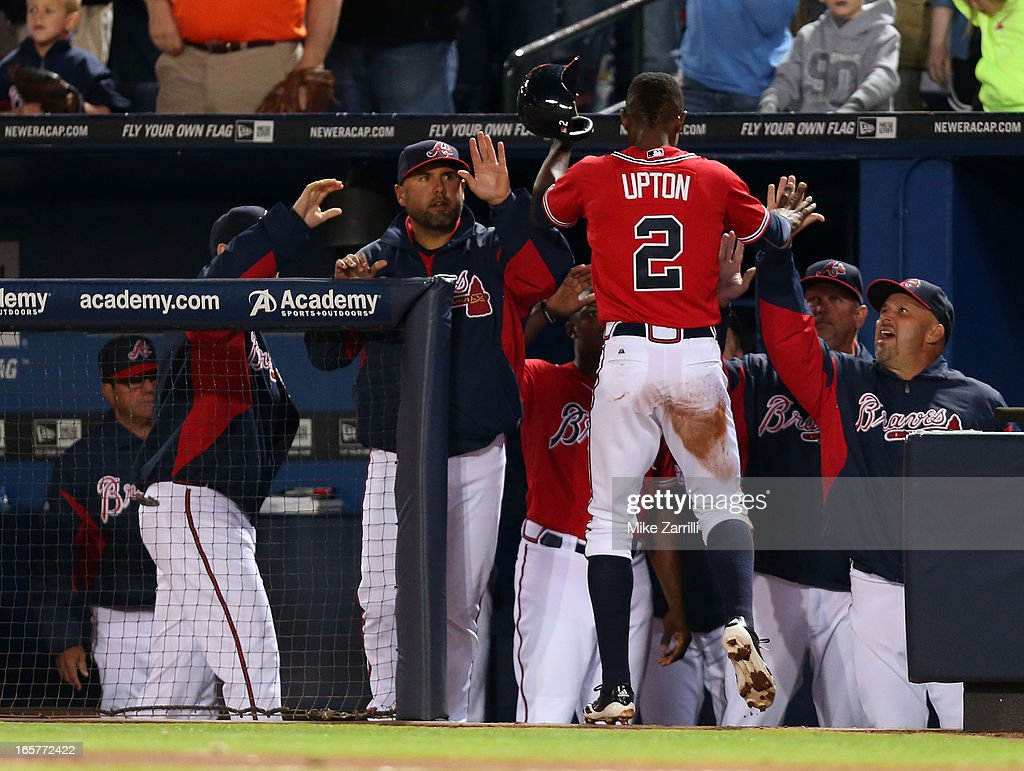 Centerfielder <a gi-track='captionPersonalityLinkClicked' href=/galleries/search?phrase=B.J.+Upton&family=editorial&specificpeople=810704 ng-click='$event.stopPropagation()'>B.J. Upton</a> #2 of the Atlanta Braves is congratulated by his teammates and manager <a gi-track='captionPersonalityLinkClicked' href=/galleries/search?phrase=Fredi+Gonzalez&family=editorial&specificpeople=686896 ng-click='$event.stopPropagation()'>Fredi Gonzalez</a> #33 (R) after scoring in the fifth inning during the game against the Chicago Cubs at Turner Field on April 5, 2013 in Atlanta, Georgia.