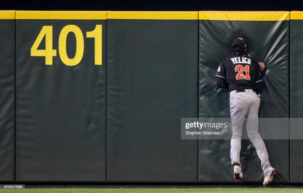 Centerfielder Christian Yelich #21 of the Miami Marlins hits the wall after making a catch on a ball hit by Jarrod Dyson #1 of the Seattle Mariners during the first inning of a game at Safeco Field on April 19, 2017 in Seattle, Washington.