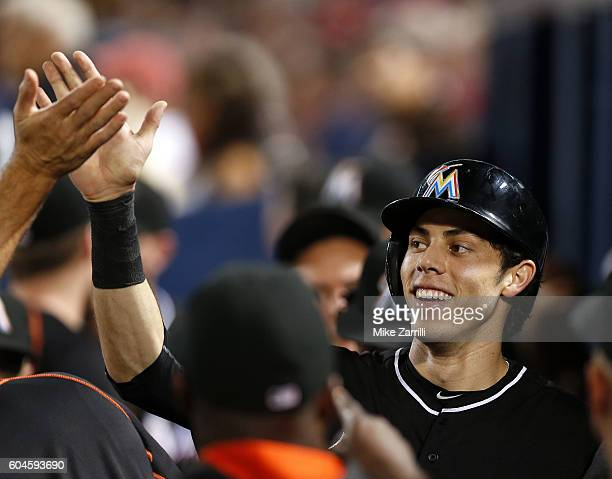Centerfielder Christian Yelich of the Miami Marlins is congratulated after scoring in the fifth inning during the game against the Atlanta Braves at...