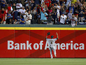 Centerfielder Coco Crisp of the Oakland Athletics loses track of a ball that bounces over the fence for a ground rule double hit by Chris Johnson of...