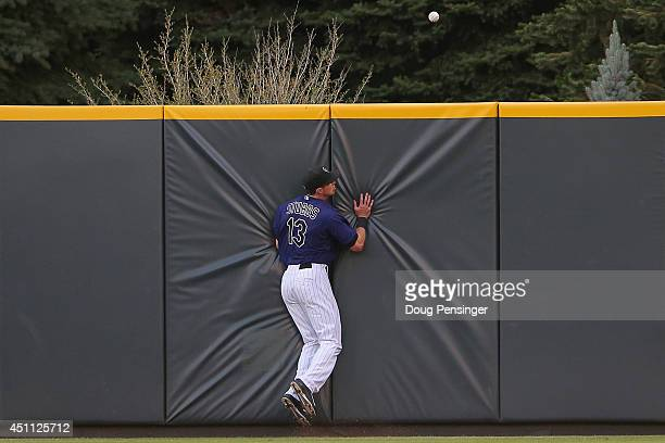 Centerfielder Drew Stubbs of the Colorado Rockies collides with the wall as he chases down an RBI double by Jhonny Peralta of the St Louis Cardinals...
