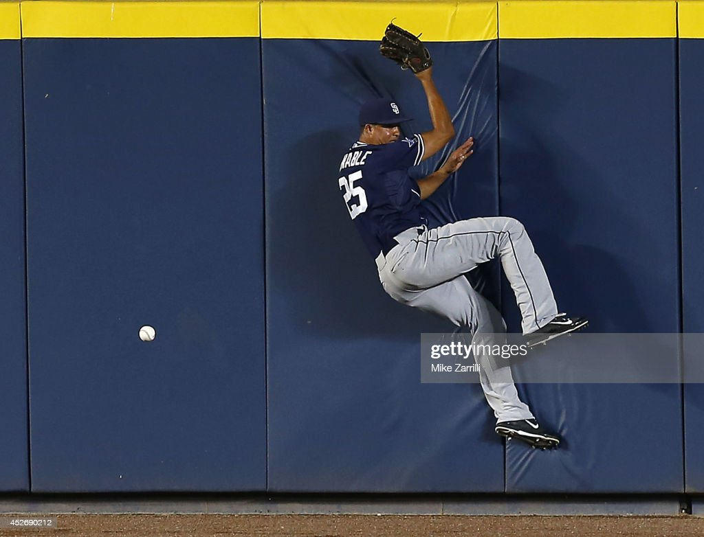 Centerfielder Will Venable of the San Diego Padres crashes into the outfield wall trying to pursue a ball hit by first baseman Freddie Freeman of the...