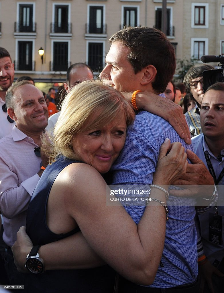Center-right party Ciudadanos leader and party candidate, Albert Rivera,(R) hugs his mother Maria Jesus Diaz after the partys final campaign meeting on Isabel II Square in Madrid on June 24, 2016 ahead of the June 26 general election. Spain votes again on June 26, six months after an inconclusive election which saw parties unable to agree on a coalition government. TORRE