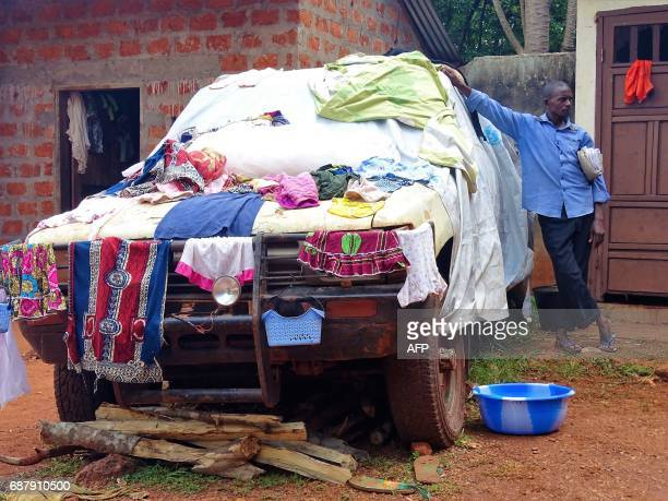 A Central African internal displaced man leans on a car where laundry is left to dry in Bangassou on May 24 2017 / AFP PHOTO / SABER JENDOUBI