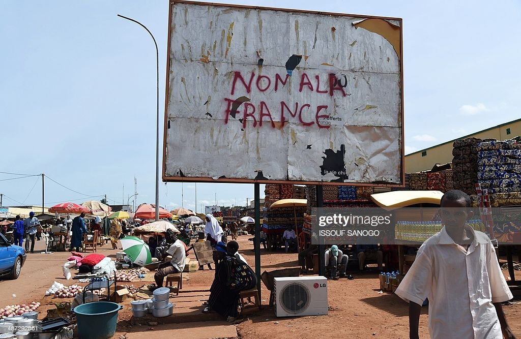 Central African market vendors sell their products near an advertising billboard covered with a graffiti inscription reading 'No to France', in the PK5 neighborhood of Bangui, on April 29, 2014. Two civilians were killed when gunmen ambushed a convoy of Muslims fleeing violence in the capital of the strife-torn Central African Republic, international peacekeepers said today.