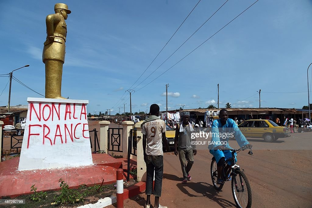 Central African men walk past the statue of Lt Georges Koudoukou (who died in Bir Hakeim while fighting with French troops during WWII), with a graffiti inscription reading 'No to France', in the PK5 neighborhood of Bangui, on April 29, 2014. Two civilians were killed when gunmen ambushed a convoy of Muslims fleeing violence in the capital of the strife-torn Central African Republic, international peacekeepers said today. AFP PHOTO / ISSOUF SANOGO