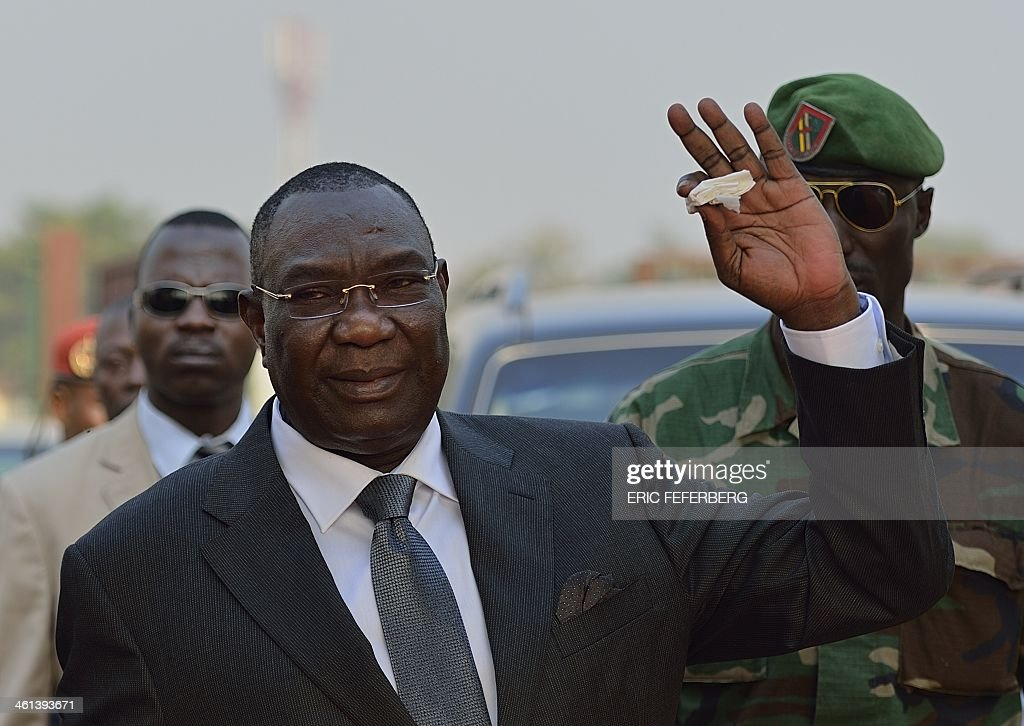 Central African president Michel Djotodia gestures as he arrives at Mpoko Bangui airport on his way to N'Djamena to attend a summit on the unrest in Centrafrica on January 8, 2014. African leaders are to meet in Chad Thursday to discuss the future of Central African Republic President Michel Djotodia, in a bid to end the sectarian violence ripping the country apart. No official agenda has been drawn up for the summit called by Chadian President Idriss Deby Itno of ten countries making up the Economic Community of Central African States (CEEAC). AFP PHOTO / ERIC FEFERBERG