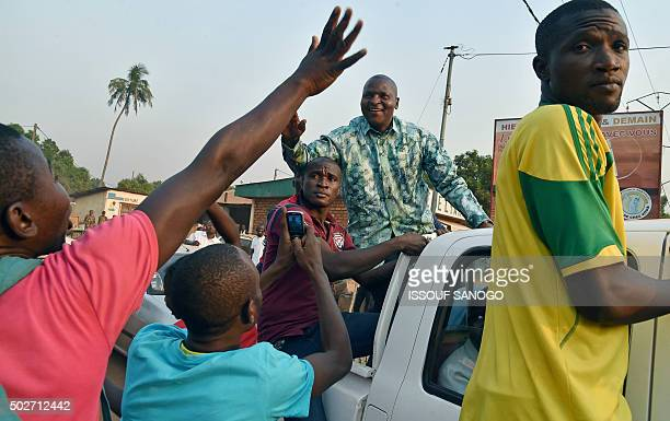 Central African presidential candidate Faustin Archange Touadera waves to supporters during a presidential campaign tour in Bangui on December 28 on...
