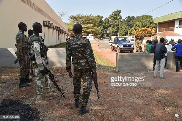 Central African Republic gendarmes and police officers stand guard outside a votecounting centre for the presidential and parliamentary elections on...