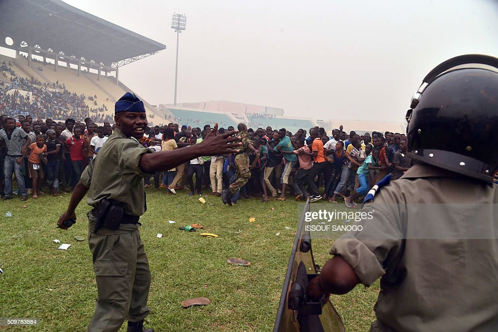 Central African Republic police officers gesture next to second round presidential candidate Anicet Georges Dologuele supporters during a presidential campaign at the Bangui stadium on February 12, 2016, ahead of the Febuary 14 presidential and legislatives elections. / AFP / ISSOUF SANOGO