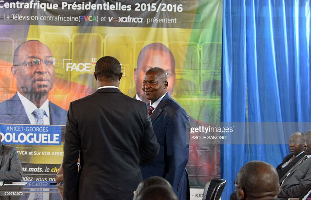 Central African Republic second round presidential candidate Anicet Georges Dologule (C) shake hands with with Faustin Archange Touadera (R) before their presidential campaign television debat in Bangui on February 12, 2016, ahead of the Febuary 14 presidential and legislatives elections. / AFP / ISSOUF SANOGO