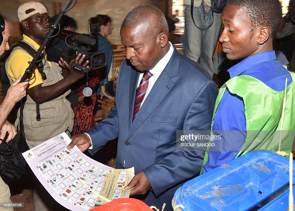Central African Republic second round presidential candidate Faustin Archange Touadera (C) looks at a ballot before voting for delayed legislative elections and a presidential run-off, at a polling station in Bangui, on February 14, 2016. The Central African Republic holds delayed presidential and parliamentary polls on February 14, with voters desperate to usher in peace after the country's worst sectarian violence since independence in 1960. / AFP / ISSOUF SANOGO