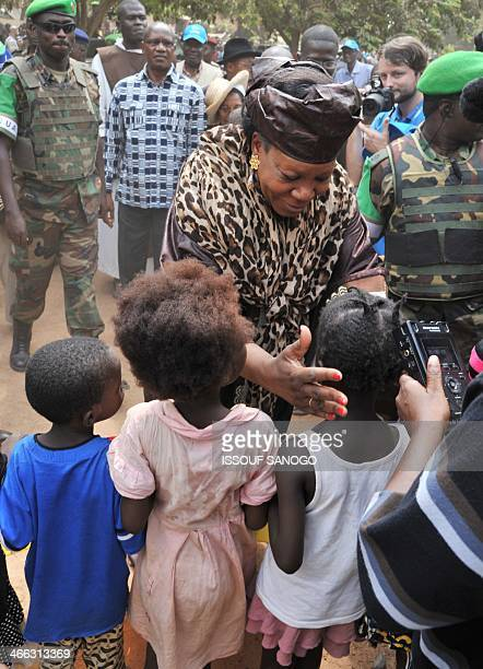 Central African Republic transitional President Catherine SambaPanza escorted by Rwandan MISCA peacekeepers meets with young children during a visit...