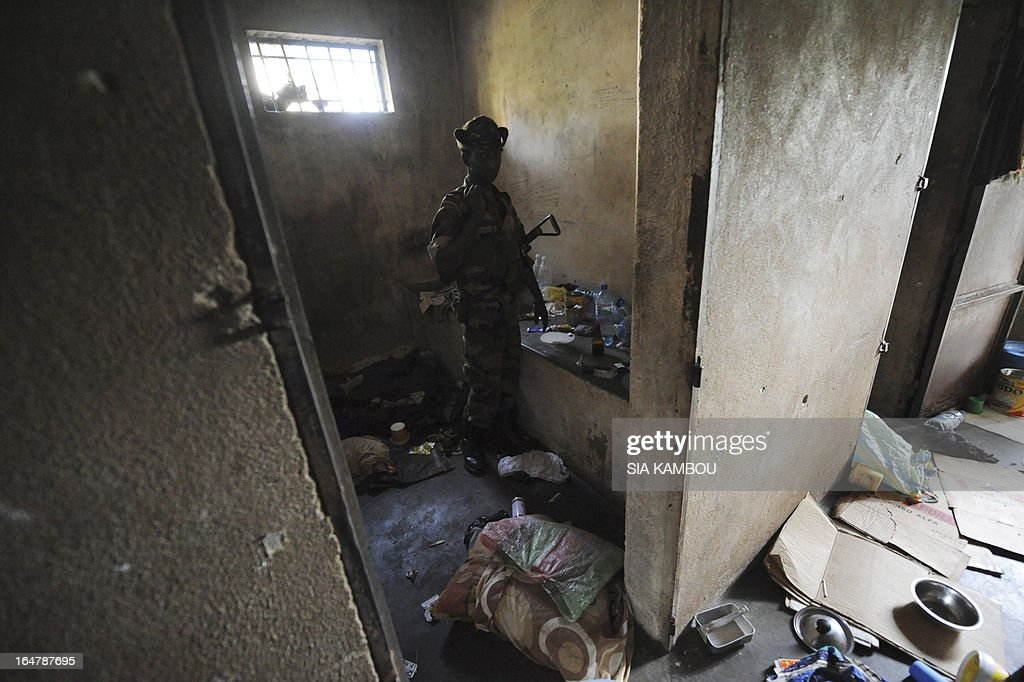 A Central African Seleka rebel, whose coalition on March 24, 2013 seized control of Bangui in a rapid-fire weekend assault that forced President Francois Bozize into exile, stands in a prison cell on March 27 at the Roux military camp in the capital, where political and military prisoners were held. Since they took control, the rebels have set up patrols to try to combat the looting -- some committed by their own members, some by bandits pretending to be rebels and some by local residents. AFP PHOTO / SIA KAMBOU