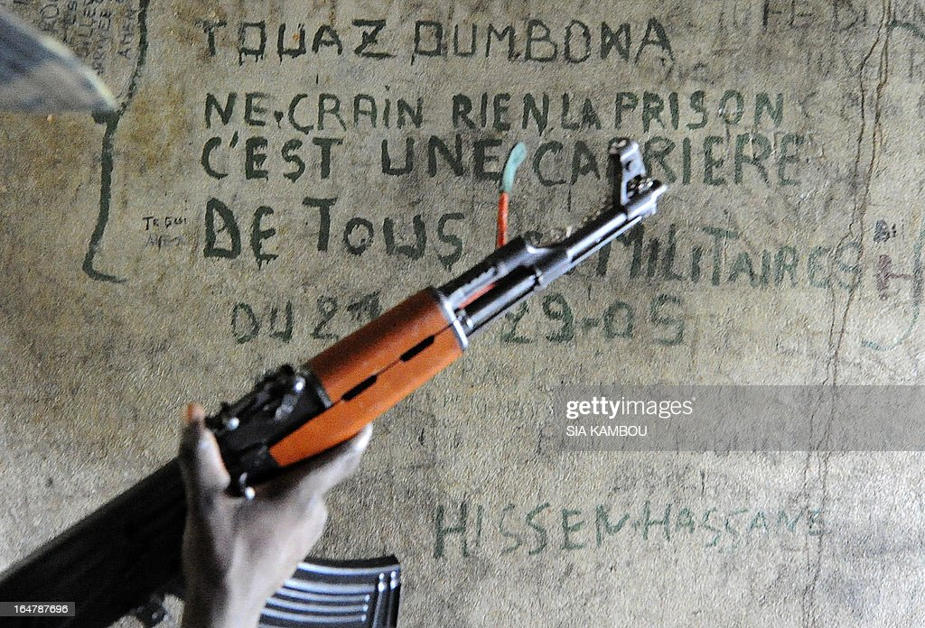 A Central African Seleka rebel, whose coalition on March 24, 2013 seized control of Bangui in a rapid-fire weekend assault that forced President Francois Bozize into exile, stands in a prison cell on March 27 at the Roux military camp in the capital, where political and military prisoners were held. Since they took control, the rebels have set up patrols to try to combat the looting -- some committed by their own members, some by bandits pretending to be rebels and some by local residents. Graffito on wall reads: 'Do not fear anything, prison is the career of all soldiers.' AFP PHOTO / SIA KAMBOU