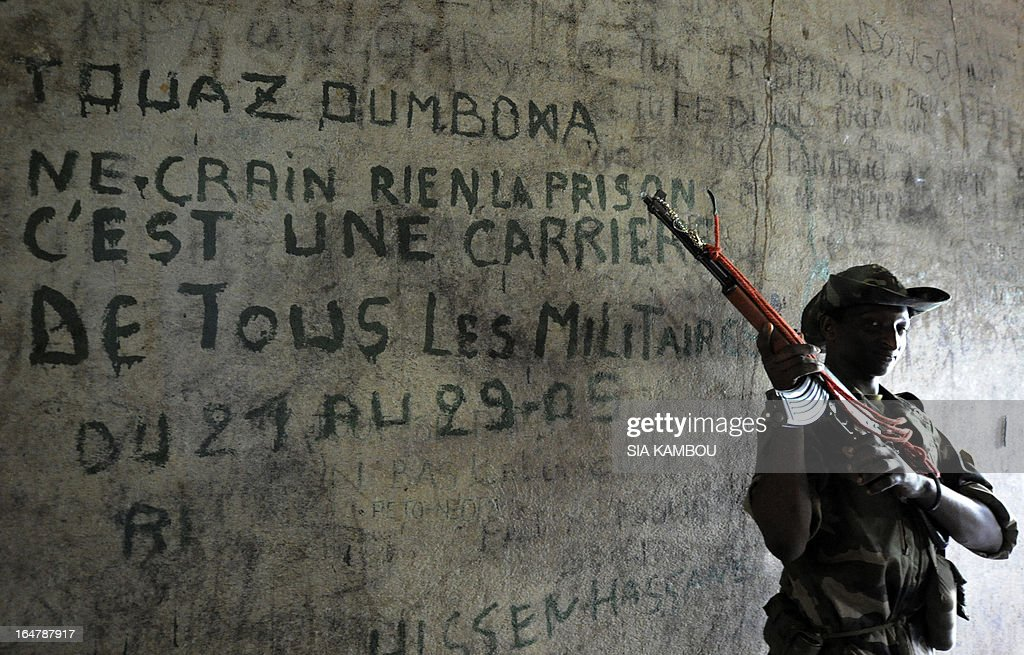 A Central African Seleka rebel, whose coalition on March 24, 2013 seized control of Bangui in a rapid-fire weekend assault that forced President Francois Bozize into exile, stands in a prison cell on March 27 at the Roux military camp in the capital, where political and military prisoners were held. Since they took control, the rebels have set up patrols to try to combat the looting -- some committed by their own members, some by bandits pretending to be rebels and some by local residents. Graffito on wall reads: 'Do not fear anything, prison is the career of all soldiers.'