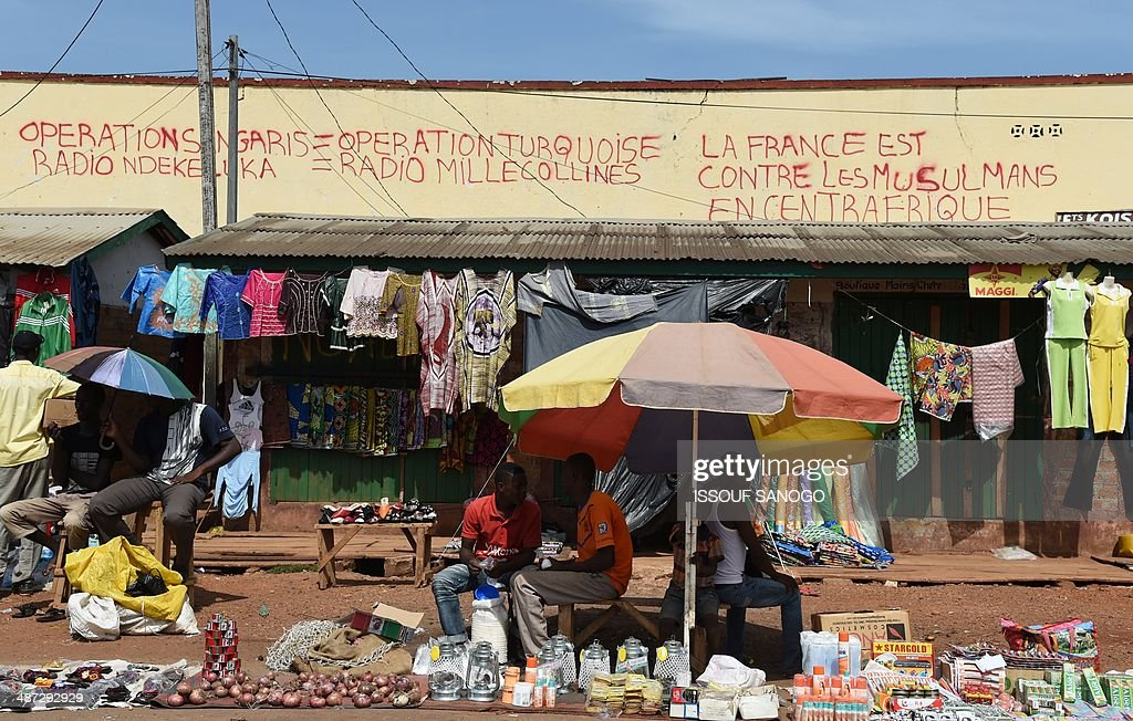 Central African street vendors sell products near a wall with a graffiti inscription reading 'France is against Muslims in Central Africa', in the PK5 neighborhood of Bangui, on April 29, 2014. Two civilians were killed when gunmen ambushed a convoy of Muslims fleeing violence in the capital of the strife-torn Central African Republic, international peacekeepers said today.